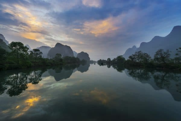 yulong river at sunset with mountains reflection in yangshuo