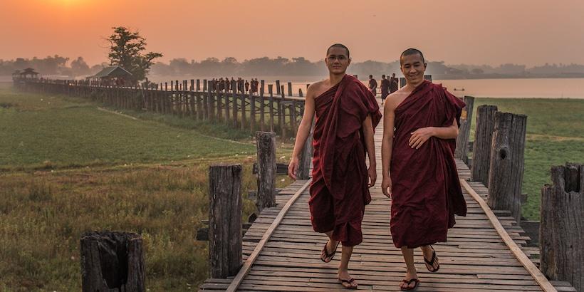 two-monks-walking-on-the-u-bein-bridge-at-sunset