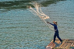 fisherman-casting-a-net-on-a-bamboo-raft