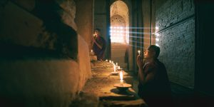 young-monks-praying-inside-a-dark-temple-in-bagan