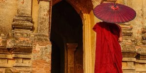 a-monk-standing-in-front-of-a-temple-in-bagan