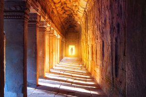 a-monk-walking-in-the-passageway-of-angkor-wat